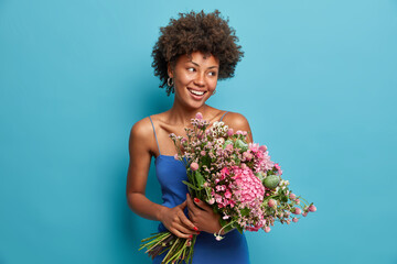 Happy teacher poses with big beautiful bouquet of flowers received from pupils, looks gladfully...