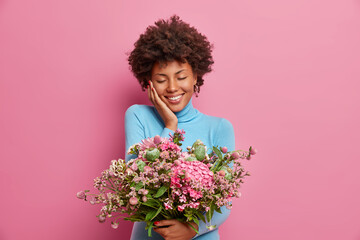 Photo of pleased touched young Afro American woman got gift for anniversary, carries big bouquet of flowers, closes eyes and smiles gently, wears blue turtleneck, isolated on pink background