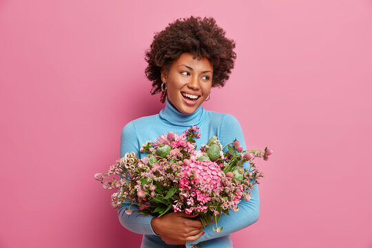 Happy ethnic Afro American woman embraces big bouquet of flowers, smiles broadly, being touched with romantic gift from boyfriend, dressed casually, isolated on pink background, has festive mood