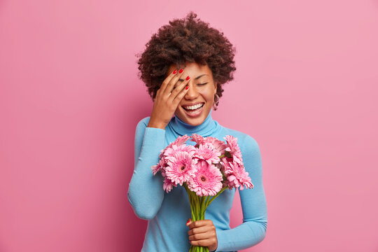 Overjoyed Afro American woman laughs out loudly, keeps palm on face, stands indoor with bouquet of gerberas, going to congratulate mother with womens day, receives flowers from unknown person