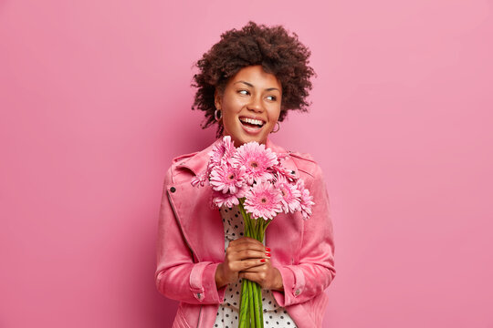 Happy sincere Afro American birthday girl receives flowers from friends, holds bouquet of gerberas, has positive festive mood, isolated on pink wall. Glad woman accepts proposal of marriage.