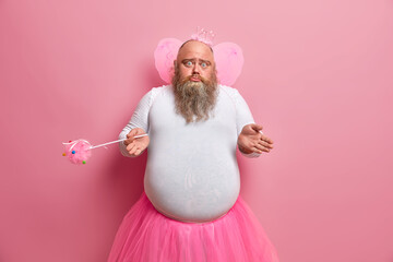 Clueless doubtful male failry wonders why his abilities disappeared, plays in performance for children, wears special costume, holds magic wand, isolated on pink background, lives at magic land