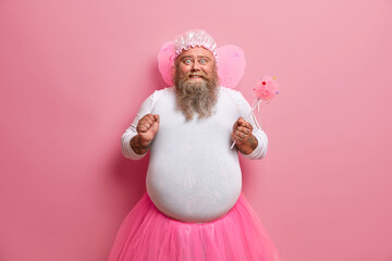 Plump bearded man has image of magic fairy, clenches fist, happy about his abilty to make things disappear, pretends being supernatural being, plays with kids on party, uses power for invisibility