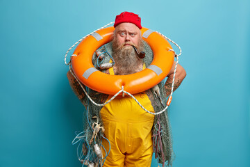 Experienced sailor carries inflated swim ring and smoking pipe, busy with vessel mainetnance,...