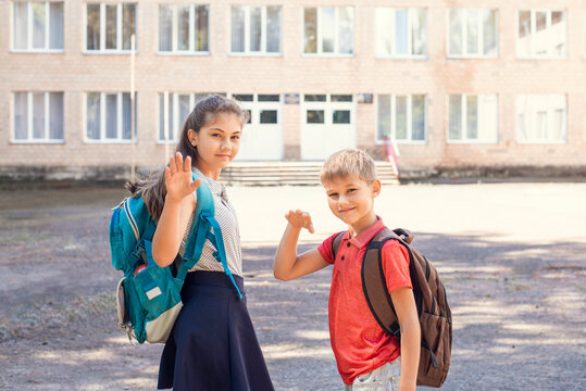 Little boy and his elder sister waving goodbye to parents on their way to school, standing in front of building of conventional school