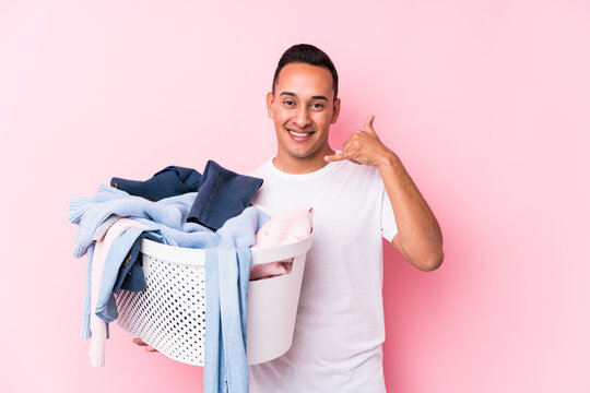 Young latin man picking up dirty clothes isolated showing a mobile phone call gesture with fingers.