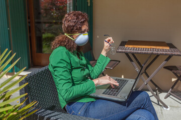 Woman sitting in a garden with antivirus mask looking at laptop searching news. People life during the pandemic