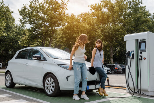 Two happy young beautiful women are talking to each other until their electric car is charging at the charging station situated in the car park.