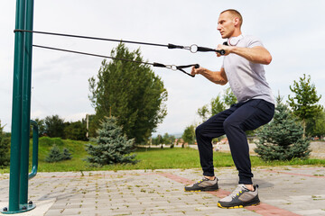 Adult caucasian man training outdoor in park in summer day - Male athlete using resistance band tubes in his daily workout routine - Real people health and fitness concept