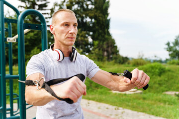 Adult caucasian man training outdoor in summer day - Male athlete using resistance band tubes in his daily workout routine - Real people health and fitness concept