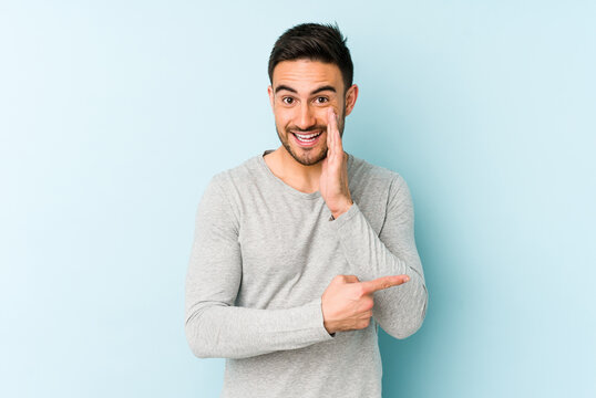 Young caucasian man isolated on blue background saying a gossip, pointing to side reporting something.