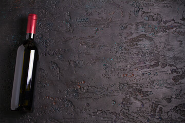 Bottle of red wine, wine glass on black background, copy space. View from above, top studio shot