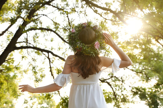Young woman wearing wreath made of beautiful flowers outdoors on sunny day, back view