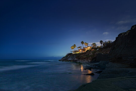 Clifftop homes overlooking the ocean at twilight with palm trees, lights reflecting in the water and a deep blue sky illuminated by distant city lights