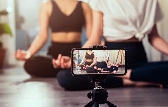 Yoga online to live streaming on a smartphone, The fitness trainer teaches exercise so that the audience via the Internet for watching tutorial lesson at home.