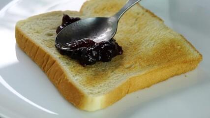 Fototapete - People using metal spoon spread blueberry jam on a toast. Spreading blueberry jam on a toast for breakfast.