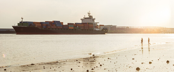 Large container vessel and city beach at the Elbe river in Hamburg, Germany during scenic sunset