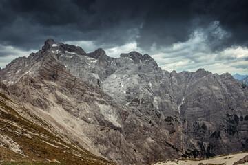 Panorama of the Cima dei Preti mountain range with dramatic cloudy sky, Dolomites, Italy