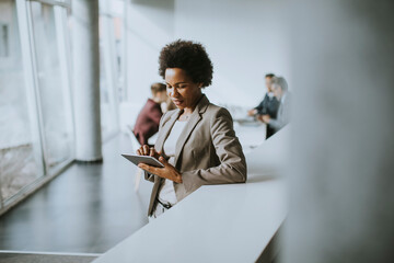 African American businesswoman standing and using digital tablet in a modern office