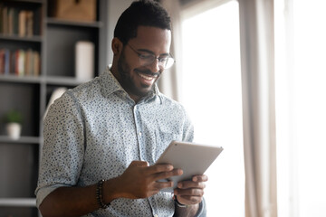 Smiling African American man wearing glasses holding computer tablet, looking at screen, playing game, browsing apps, chatting with friends in social network, having fun with gadget close up