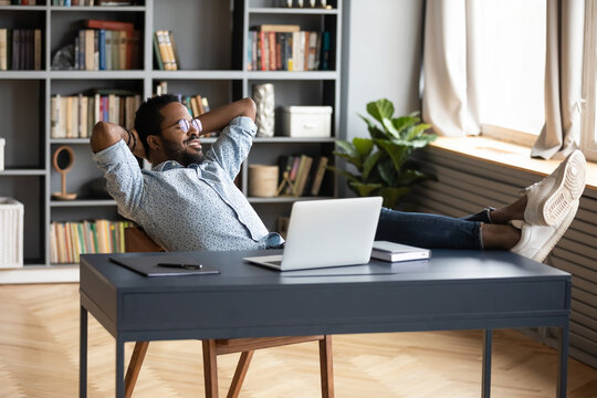 Smiling peaceful African American man resting, leaning back in office chair, sitting with hands on desk with laptop, calm lazy young businessman student relaxing after work done at workplace