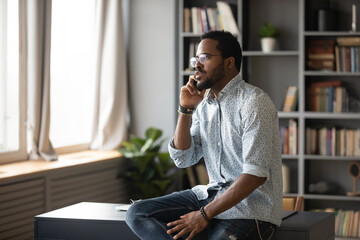 Serious African American man wearing glasses talking on phone, making call, sitting on work desk,...