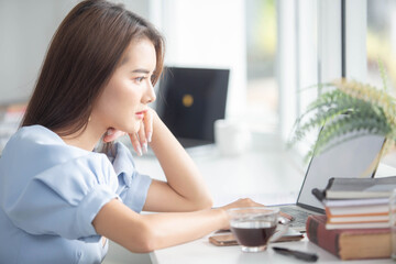 Protrait of Beautiful businesswoman sitting at desk and working with laptop smartphone and computer.