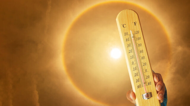 Heat wave background glowing sun on solar halo orange sky with thermometer displaying high Beyond 40 degrees celsius,global warming.