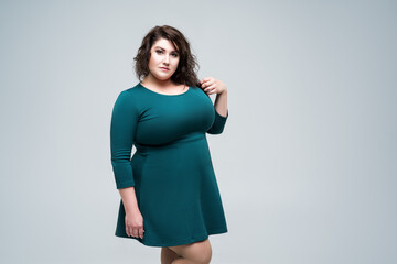 Plus size fashion model in green dress, fat woman on gray background, body positive concept