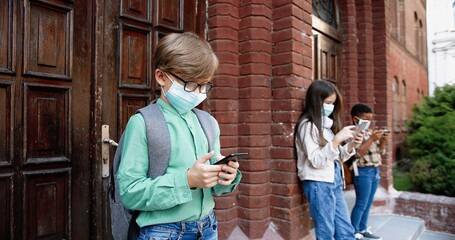 Portrait of mixed-races junior students standing near school and typing on smartphones. Caucasian boy in mask browsing on cellphone. Girl with African American kid on background. Quarantine concept