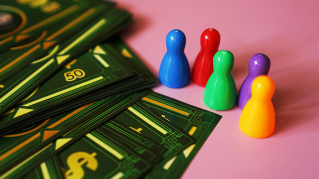 Board game Monopoly with money and plastic chips. No logos or visible brands - pink background