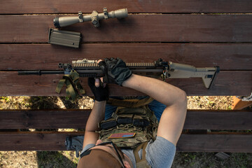Above view of skilled young American man in gloves sitting at wooden table and assembling rifle...