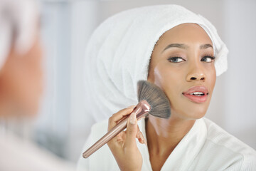 Attractive young Black woman in bathrobe and towel on her head applying make-up in front of mirror