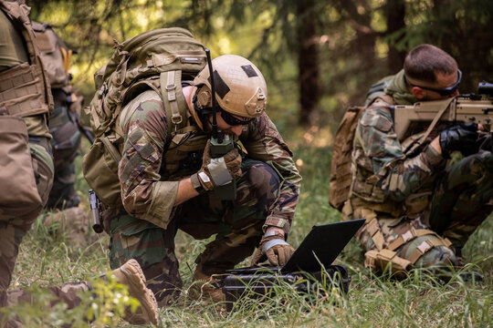 Busy soldier with backpack using military laptop while passing information through radio device in forest