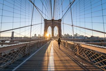 Woman walking across the Brooklyn Bridge at sunrise, New York City, USA