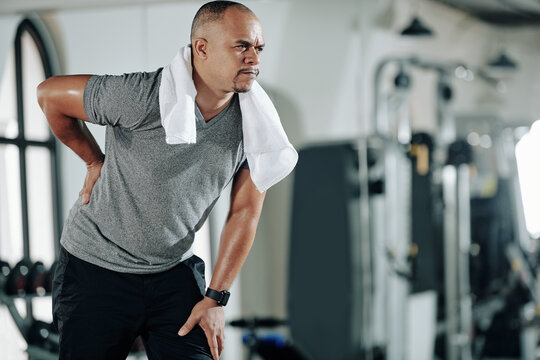 Mixed-race man suffering from low back pain after training in gym