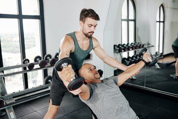 Serious fitness trainer helping mature man to do dumbbell fly on bench in gym