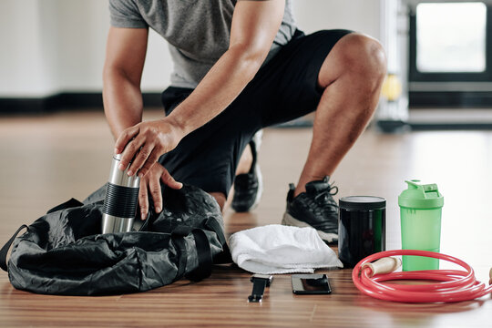Cropped image of sportsman packing bag on gym floor after training