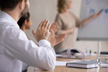 Close up happy young businessman clapping hands with mixed race colleagues, thanking older mature...
