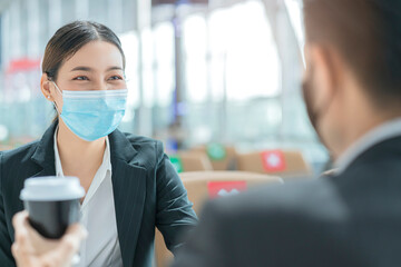 businessman and woman with face mask protection casual meeting at social distancing seat at airport...