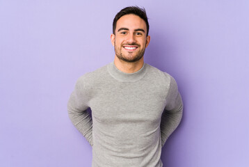 Young caucasian man isolated on purple background happy, smiling and cheerful.