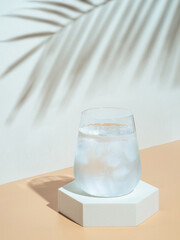 Cold water with ice in tumbler glass on hexagon pedestal. Mockup for drink in fashion trendy style with tropical leaf shadow. Modern still life with glass. Copy space. Health, beverage, summer concept