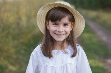 Happy little girl on the road. Cute smiling girl in a white dress stands near field