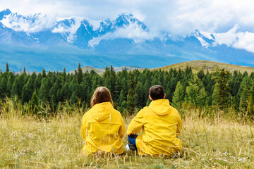 Fototapeta Young couple of tourists in yellow raincoats sit and look at the snowy Alpine mountains. Travel and vacation concept