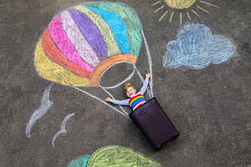 Happy little toddler girl flying in hot air balloon painted with colorful chalks in rainbow colors...