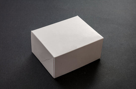 Closed white package box, blank advertise template for products packaging, on black background.
