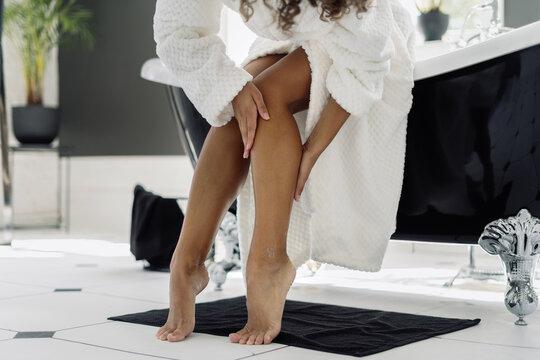 African american woman in bathrobe spending morning in bathroom