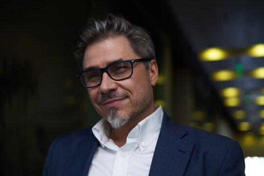 Indoor portrait of white man wearing eyeglasses. Dark colors.