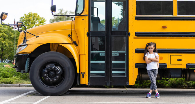 Cute girl with a backpack standing near bus going to school posing to camera pensive close-up