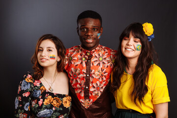 Peaceful Concept of friendship and peace between countries: African man and two Latin ladies in national clothes show hug together with body arts flags Congo, Brazil, Ecuador